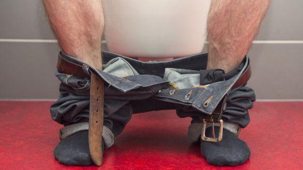Piernas de un hombre sentado en el inodoro