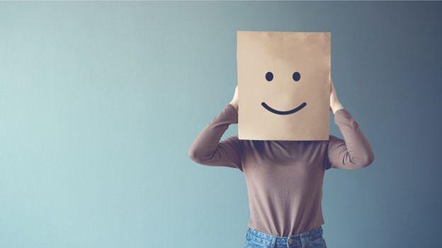 Persona con una bolsa con cara sonriente en la cabeza