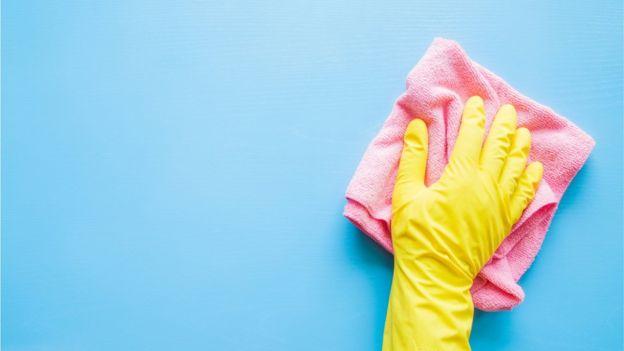 Mano limpiando una superficie
