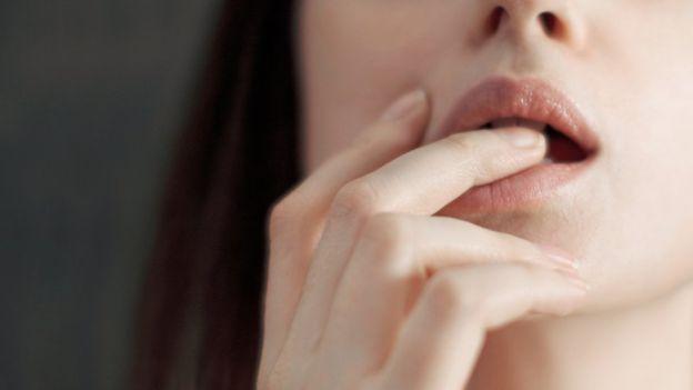 Mujer tocándose la boca