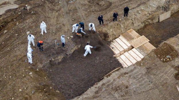 Cuerpos siendo enterrados en fosas comunes.
