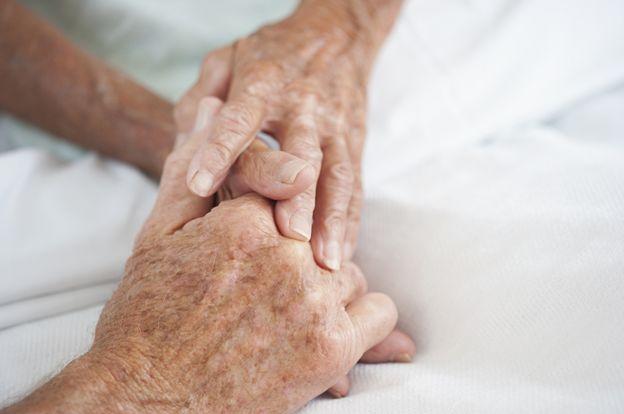 Una pareja mayor sosteniéndose las manos