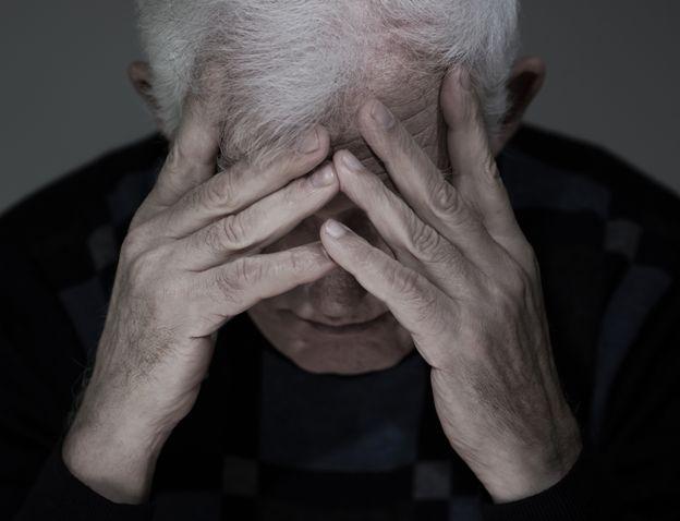Un hombre mayor se toma la cabeza
