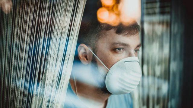 Paciente de covid-19 con mascarilla, mirando por una ventana.