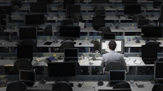 Hombre trabajando de noche, solo en una oficina