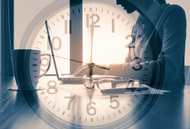 Una mujer trabaja con un portátil con la imagen de un reloj superpuesto