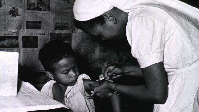 Una enfermera administra la vacuna BCG a un niño en Vietnam en la década del 50.