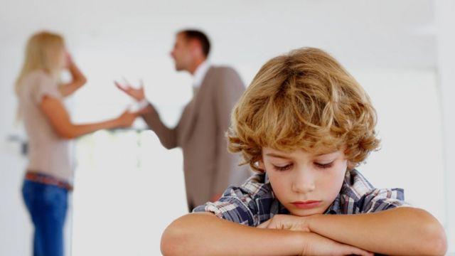 Un niño apesadumbrado escucha una discusión de sus padres en segundo plano
