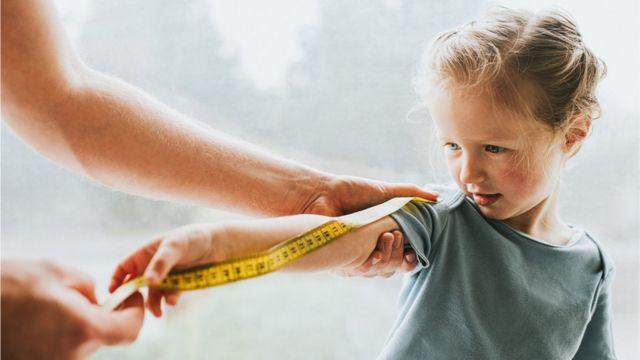 Una niña con una cinta métrica